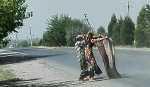 Senyores espolsant catifes a la carretera