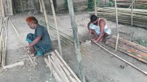 Primer l'home de l'esquerra obre les canyes per la meitat. Després el de la dreta pica i elimina els nusos per poder aplanar la canya