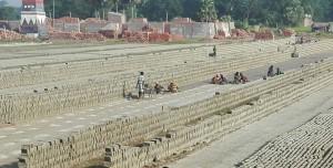 Aquest grup de treballadors agafen el fang homogeni i emprant uns motlles fan centenars de totxos que deixen a assecar