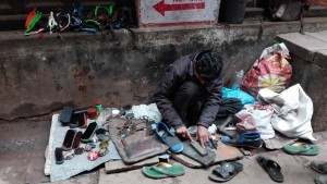 El nostre sabater a la seva 'botiga', al mig d'un carreró. Un cop amb un mànec de fusta i un tros de metall, ara toca esmolar la punta