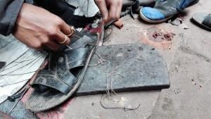 Per fer el forat que serà el ganxo per cosir, agafa el fil i el va passant repetidament fins erosionar la punta metàl·lica