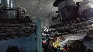 La gent, a part d'omplir tots els seients i espais horitzontals del tren seient on sigui o anant d'empeus, també seuen o s'estiren als prestatges que son per deixar l'equipatge. Per 'respecte' als passatgers que queden sota seu, es treuen les sabates i les deixen sobre els ventiladors que ara a l'hivern no funcionen. La foto la faig des d'un aquests prestatges veient com un altre passatger ho converteix en el seu llit particular.