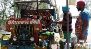 Fent un suc de canya de sucre amb una premsa que funciona agafada a un motor d'una mena de vehicle