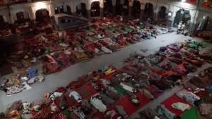 Persones dormint al terra i a l'aire lliure a un edifici annex al temple