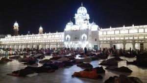 Persones dormint al terra i a l'aire lliure a la plaça davant el temple