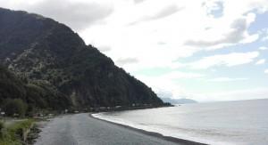 Típica platja de pedres amb parets i parets de muntanyes plenes de vegetació a tocar de l'aigua
